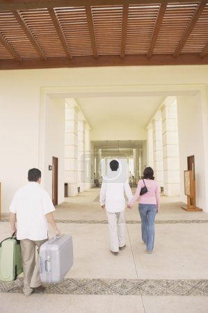 Couple walking out of hotel lobby with porter carrying luggage