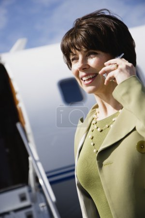 Businesswoman using cell phone in front of private airplane