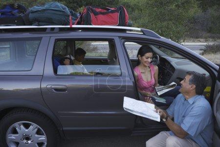 Man examining map by his family minivan