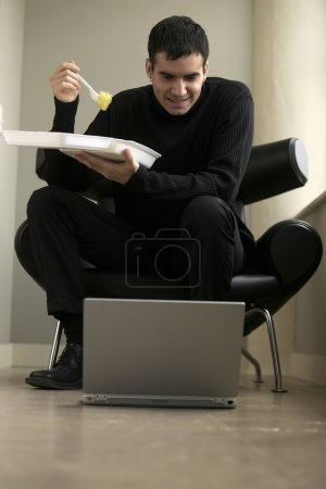 Businessman eating take out with laptop