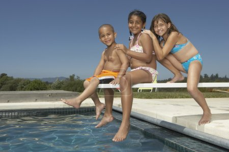 Young children smiling for the camera on a diving board