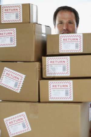 Studio shot of man behind returned packages