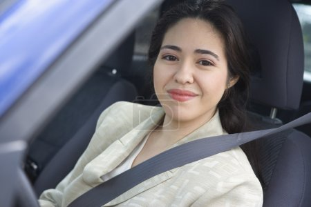 Portrait of woman sitting in car wearing seatbelt