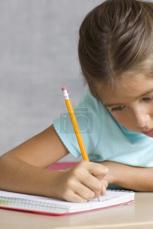 Close up of girl writing in notebook