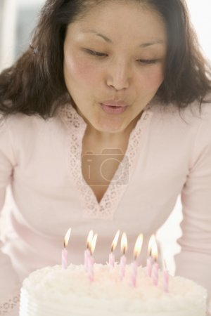 Asian woman blowing out birthday candles