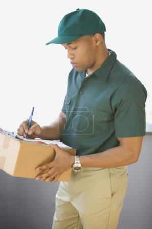 Profile of delivery man writing notes and holding box