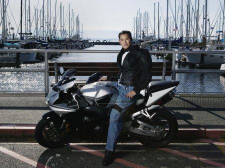 Young man on motorcycle at marina