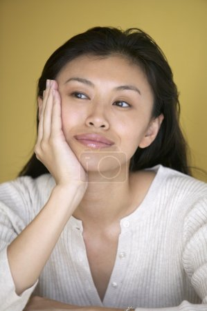 Young woman thinking with chin in hand