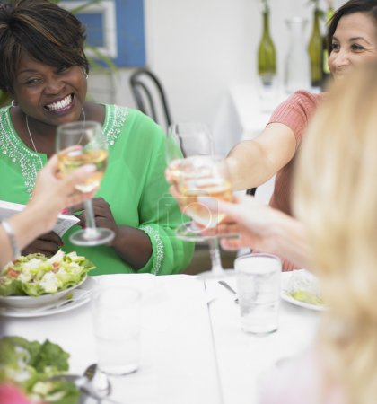 Young women toasting each other at a restaurant