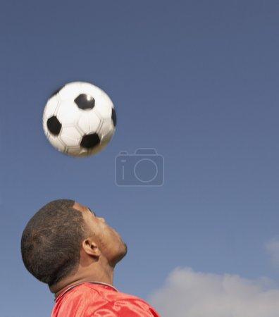 Man bouncing soccer ball off of head