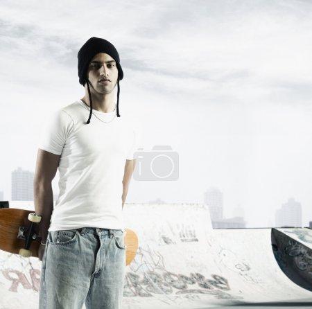Portrait of man holding skateboard