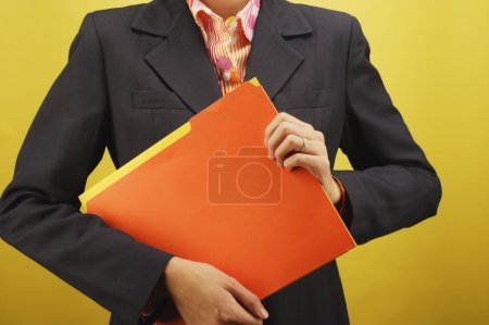 Midsection of businesswoman holding files