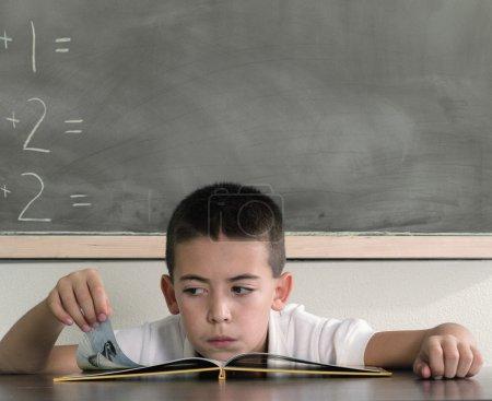 School boy reading book