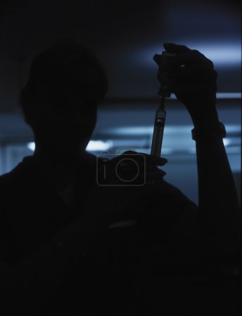 Silhouette of nurse filling syringe