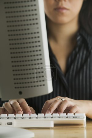 Young woman typing on keyboard