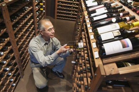 Man pulling wine bottle off shelf
