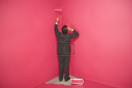 Man painting wall in corner of room