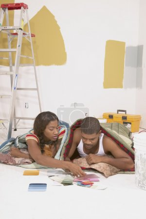 Couple looking at paint samples in sleeping bags
