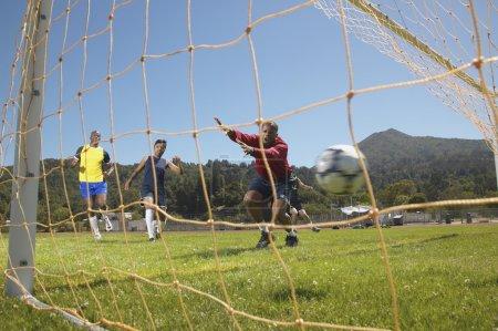 Men scoring goal in soccer game