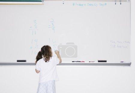 Girl writing on board in classroom