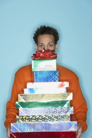 Young man behind stack of gifts