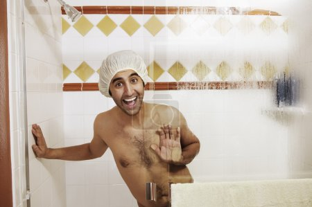 Young man wearing a shower cap in the shower