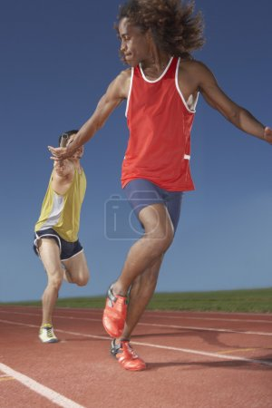 Two male runners in relay race