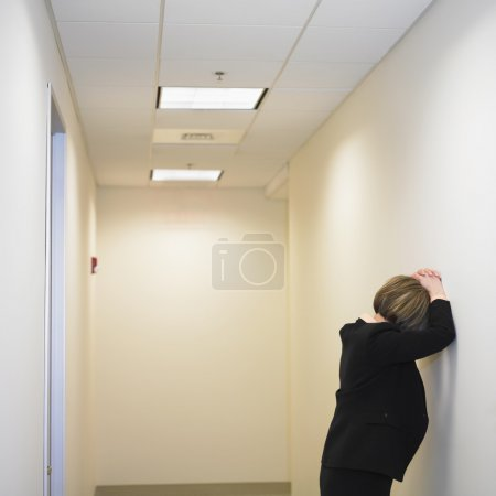Businesswoman leaning against wall
