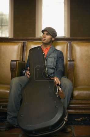Man sitting with guitar case