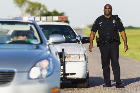Policeman walking toward stopped convertible