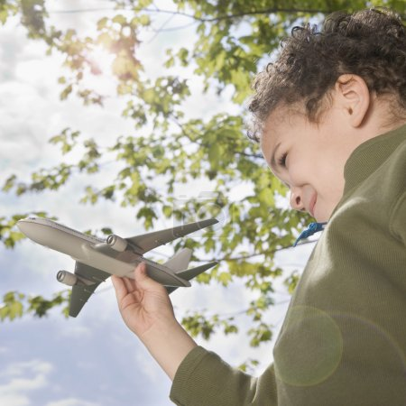 Boy standing outside with toy plane