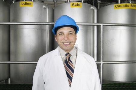 Portrait of man wearing hardhat and lab coat