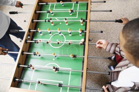 Two boys playing foosball