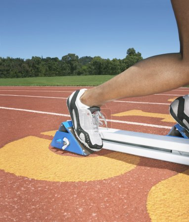 Side view of track athlete in starting blocks