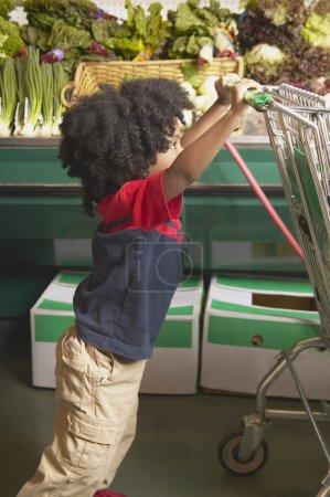 Young African American boy pushing shopping cart