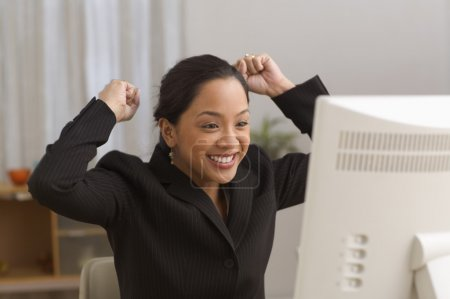 Businesswoman cheering in front of computer