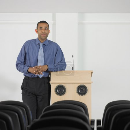 Businessman leaning on podium