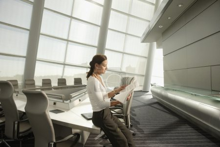 Businesswoman reading paperwork in conference room