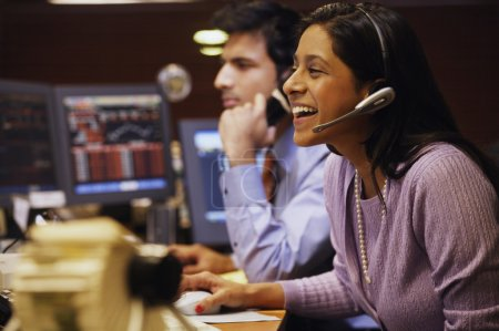 Businesswoman laughing while talking on a headset