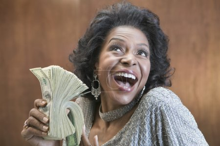 Close up of African American woman holding stack of 100 dollar bills