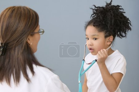 Young Asian girl with stethoscope and female doctor