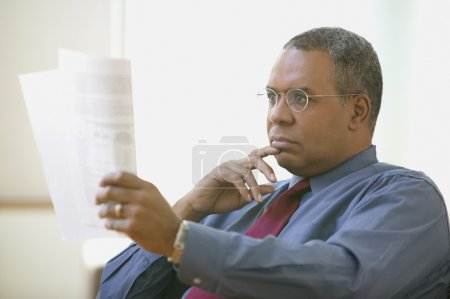 Man sitting while reading paperwork