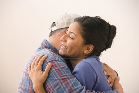 Portrait of young adult woman hugging her father