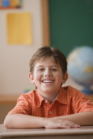 Young student laughing at his desk