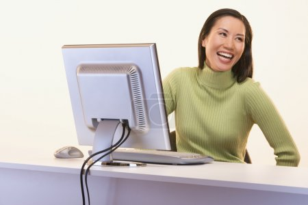 Businesswoman laughing while sitting at computer