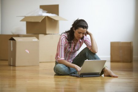 Young adult woman sitting on floor with computer with moving boxes