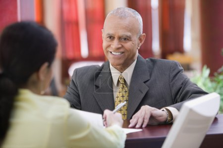 Businessman smiling at receptionist