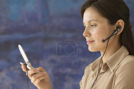 Side view of woman holding cell phone with earpiece