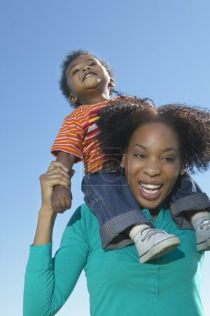 Low angle view of woman with young son on shoulders