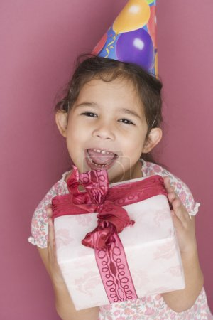 Portrait of girl with wrapped gift and birthday hat